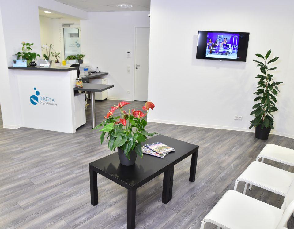 Wartebereich der Radyx Physiotherapie Leonberg mit dunklem Boden und hellen Möbeln.